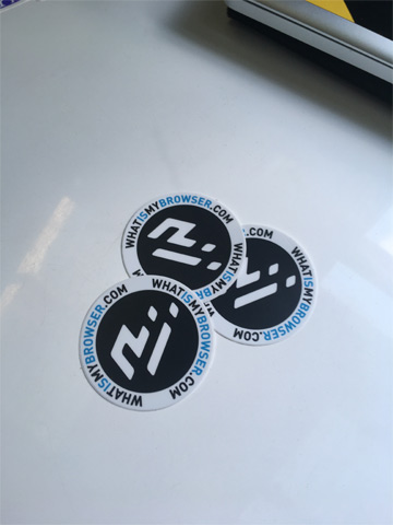 Photo of three vinyl whatismybrowser.com stickers on a desk